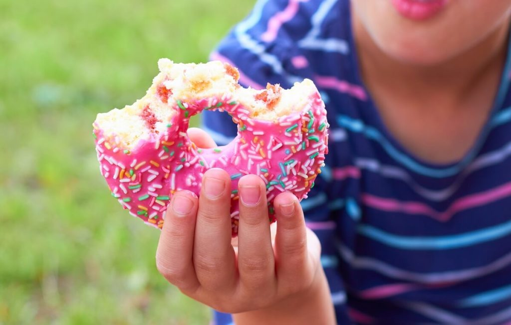Kind isst Donut ungesunder, gekaufter Pausensnack
