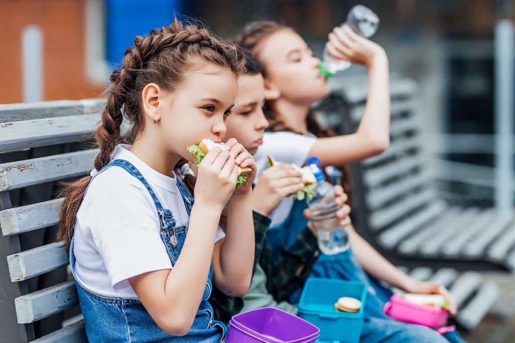 Pausenbrote Ideen Mädchen auf Bank in der Pause essen Brotzeit