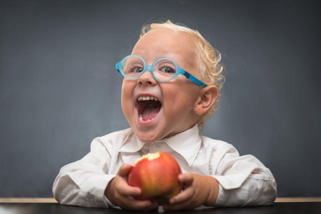 Schlaues Kind isst gesunden Apfel und freut sich