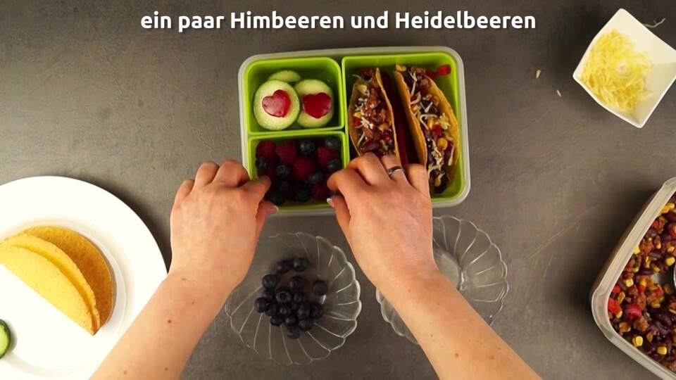 Himbeeren und Erdbeeren in die Lunchbox hinzufügen für das Essen zum Mitnehmen für Arbeit, Schule oder Uni